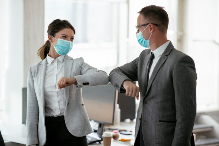 Businessman,And,Businesswoman,With,Medical,Mask,In,Office.,Greetings,In